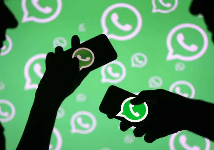 viele WhatsApp Logos, zwei Silhuethen von einem Mann und einer Frau, die durch WhatsApp unterhalten