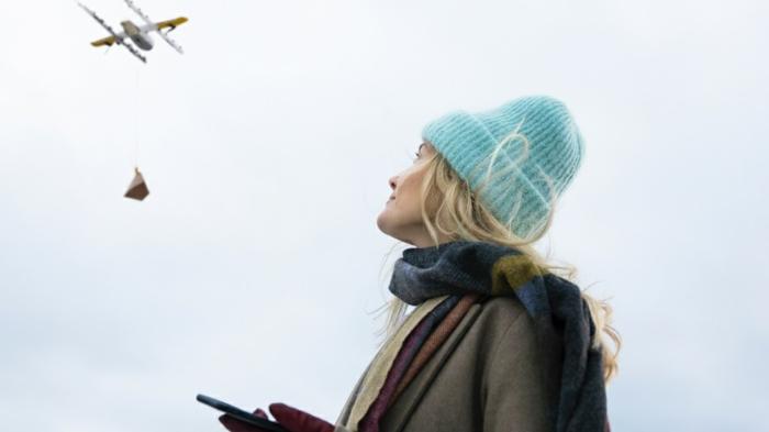 eine Frau mit blauem Mütze und blondem Haar hat durch App bestellt und jezt wartet sie auf die Drohne, Wing Drohnen