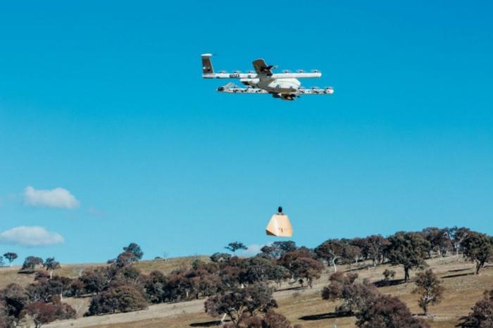 eine Drohne von Wing Drohnen fliegt über einen Hügel, ein Paket ist fertig für Lieferung