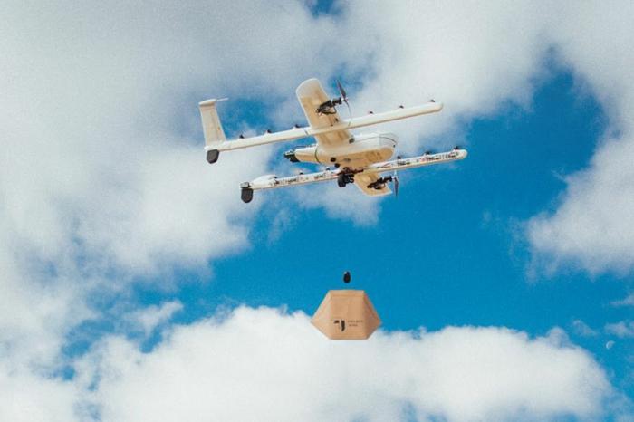 eine Drohne von den Wing Drohnen, Wolken im Himmel, ein kleines Päckchen hängt davon