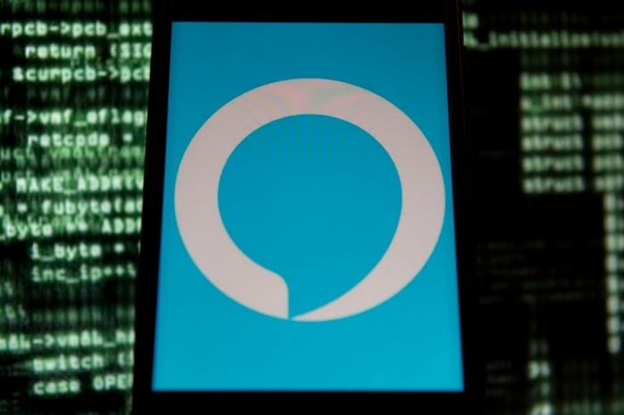 Alexa App auf Smartphone über einem Bildschirm von Windows, viele kleine grüne Buchstaben auf Hintergrund