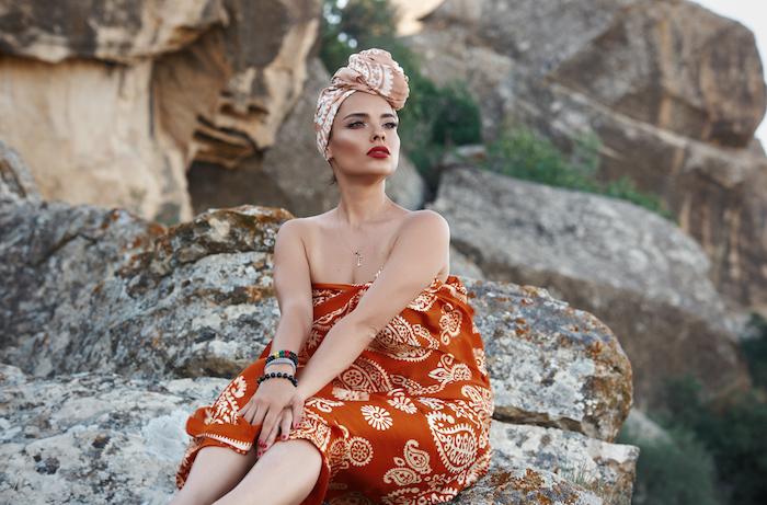 Kopftuch binden Ideen, schöne Frau sitzend auf Felsen, rotes trägerloses Kleid und Kopftuch