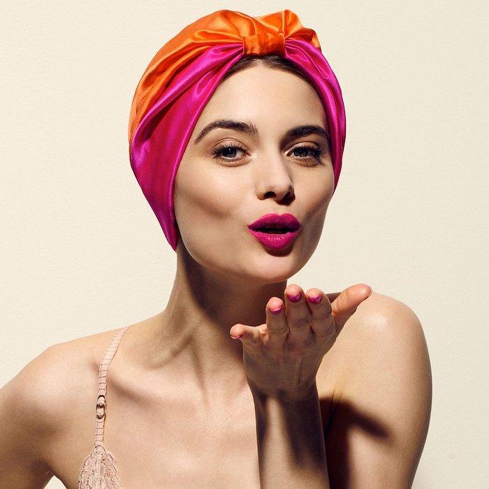 Kopftuch aus Satin in Orange und Violett, violett Lippenstift und schwarze Mascara