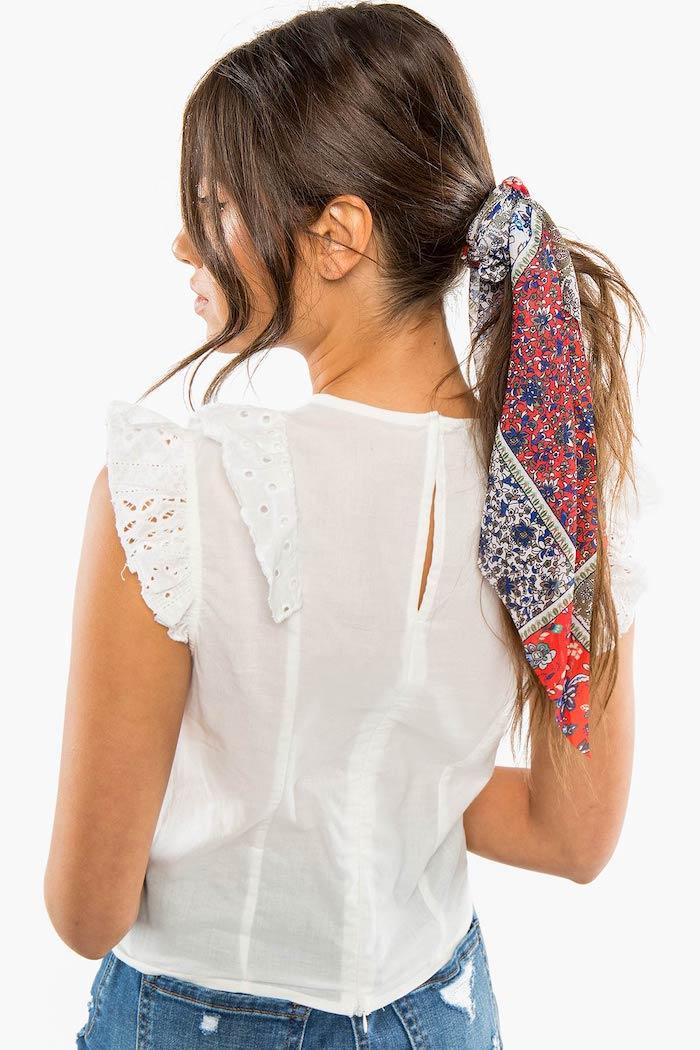 Weißes Top mit Spitzenelementen und Jeans, niedriger Zopf mit Tuch, lange braune Haare
