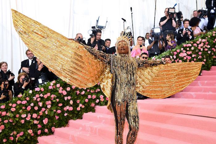 treppen mit einem pinken teppich, der sänger billy porter mit einem goldenen kostüm mit langen goldenen federn und flügeln, met gala