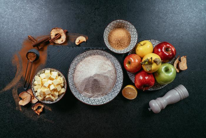Zutaten für Apfelkuchen Rezept, Äpfel und Zitrone, Butter und Vollkornmehl, Zimt und Rohrzucker