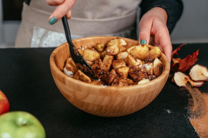 Äpfel mit Zitronensaft Maisstärke Kokosnusszucker Zimt und Vanilleextrakt mischen