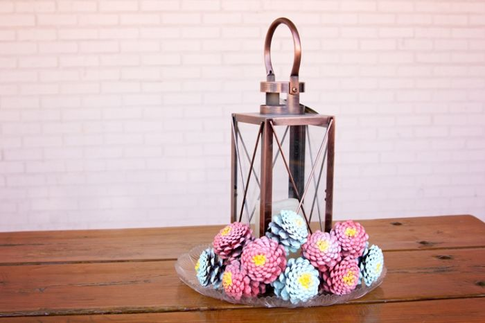 herbstdeko basteln, zapfen in bunten pastellfarben gestalten, in einem teller rund um einer lampe gestalten
