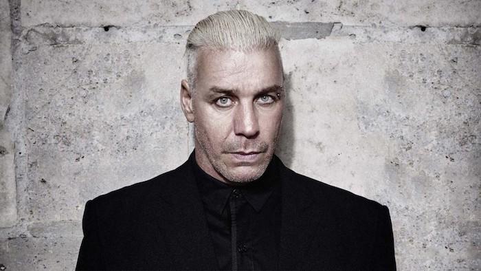 till lindemann, ein mann mit blauen augen und blondem haar und einem schwarzen hemd und mantel, weiße wand, rammstein