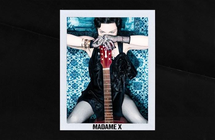 eine frau mit großer roten gotarre und einem schwarzen haar und schwarzem kleid, das neue album von der sängerin madonna namens madame x