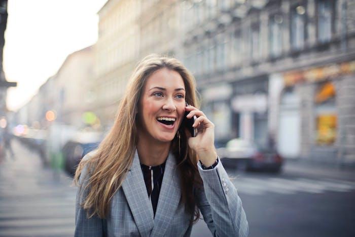 eine junge frau, die per handy telefoniert, frau mit einem grauen sakko und langem blondem haar, straße und viele autos