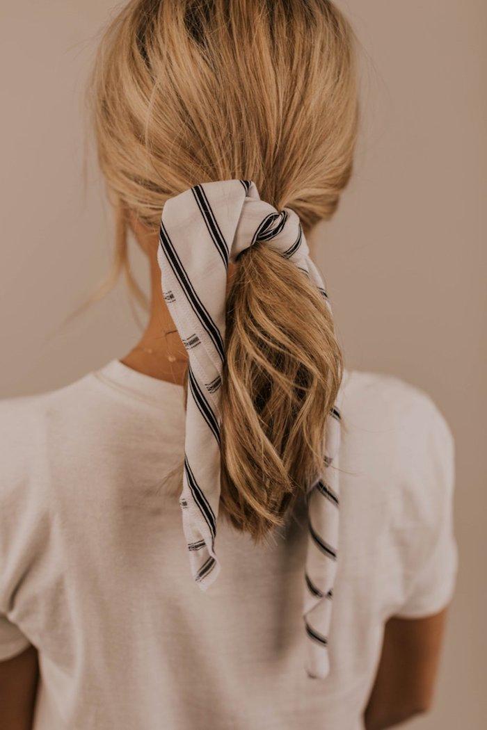 Gestreiftes Tuch in Weiß und Schwarz, lange blonde Haare, weißes Shirt