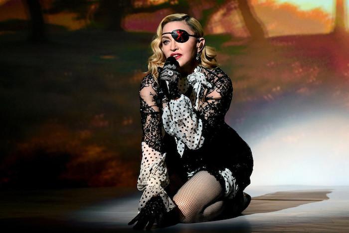 die sängerin madonna mit langem blondem haar, einem schwarzen kleid und schwarzen handschuhen, eine frau mit einer schwarzen augenklappe mit rotem x, madame x