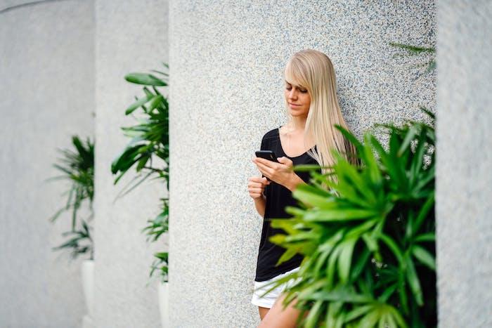 junge frau mit blondem langen haar und einem kleinen schwarzen haar, große weiße blumentöpfe mit großen pflanzen mit grünen blättern