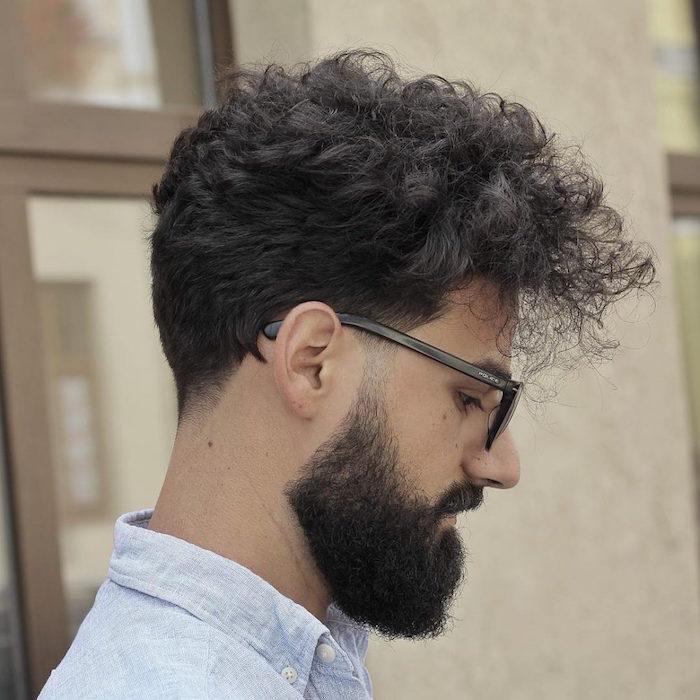 undercut mit übergang bei einem mann mit schwarzem und lockigem haar, lesebrille, hipster mode