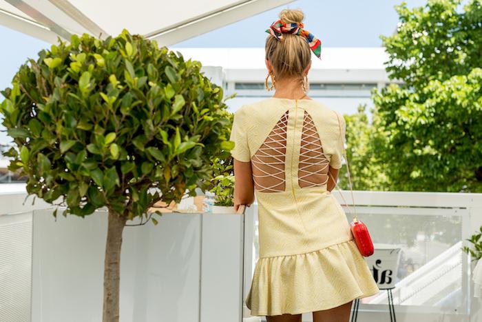 Dutt Frisur mit buntem Tuch, gelbes Sommerkleid und rote Handtasche, goldene Ohrringe