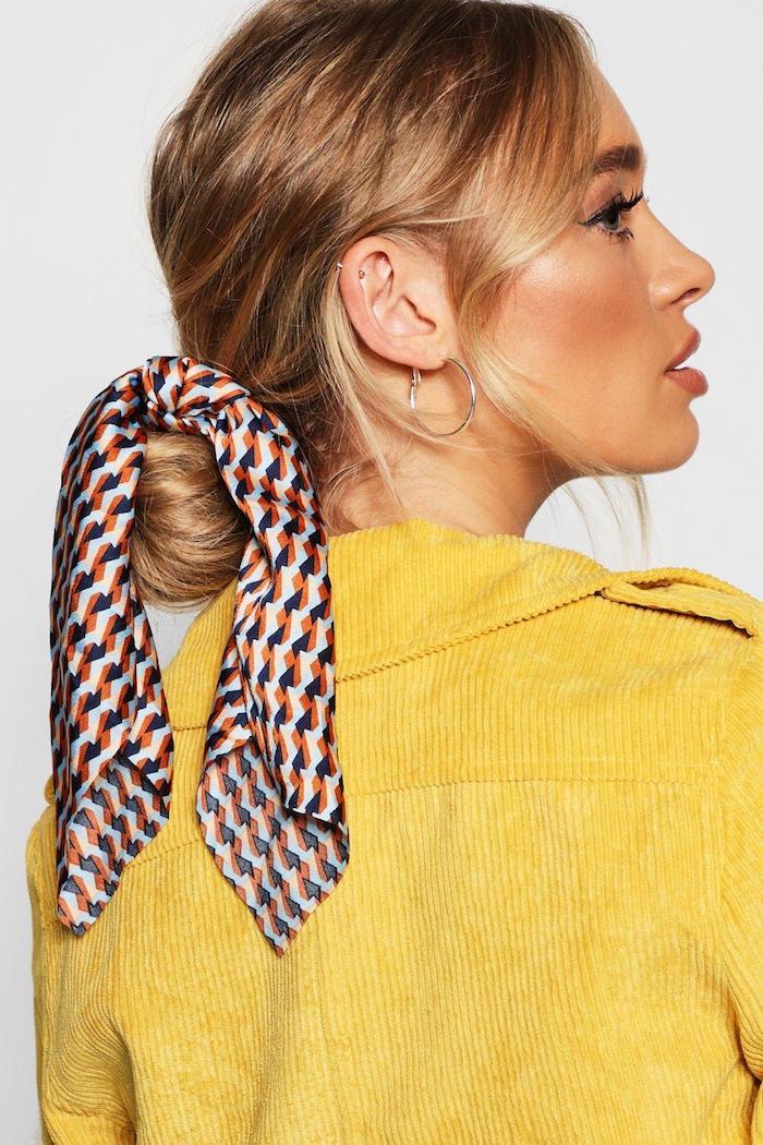 Niedriger Dutt mit Tuch, lange goldblonde Haare, gebräunter Teint, gelbe Jacke