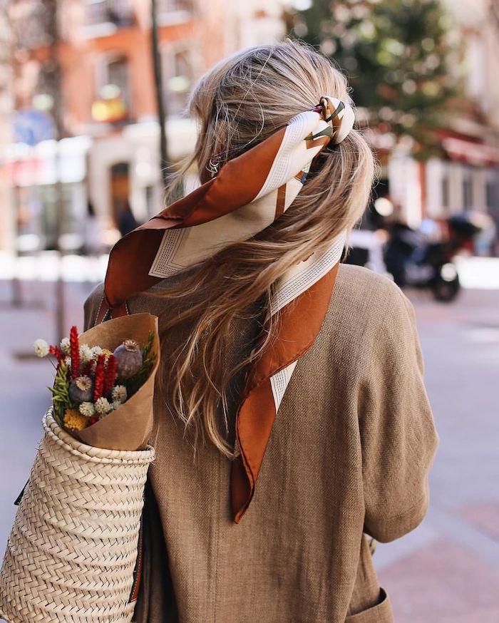 Lange blonde Haare, Kopftuch in Braun und Weiß, brauner Sakko und Rattantasche