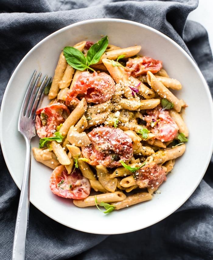 glutenfrei kochen, pasta mit romaten und basilikum, veganer mittagessen, großer weißer teller, gabel