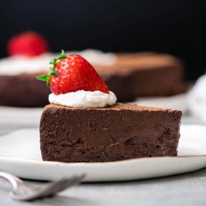 truffle cake mit schokolade dekoriert mit sahne und erdbeeren, glutenfreier veganer kuchen, dessert mit schokolade