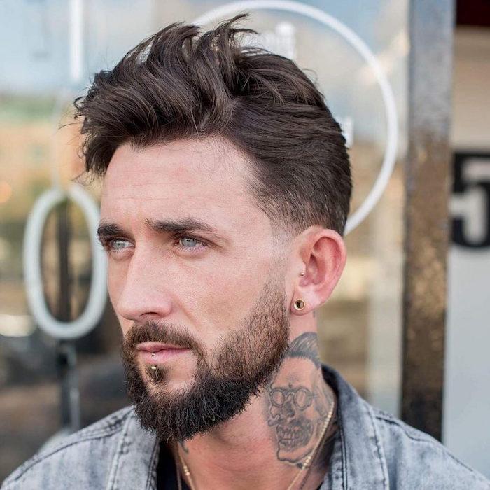 männerfrisuren 2019 style bad boy, mann mit blauen augen, schwarze haare, tattoo am hals und jeansjacke