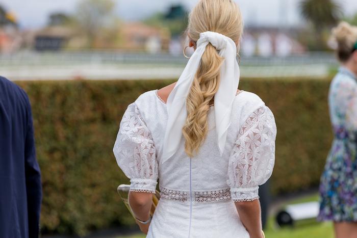 Weißes Spitzenkleid und weißes Tuch, blonde lange gewellte Haare, goldene Ohrringe