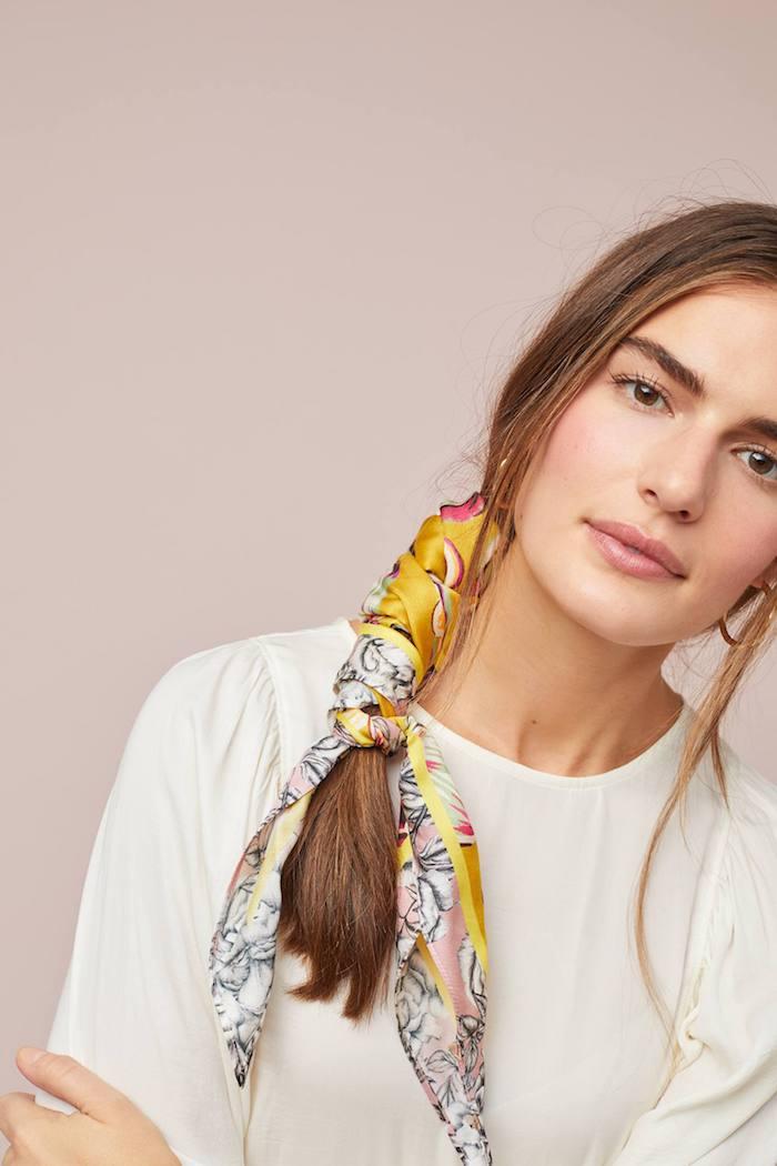 Weiße Bluse mit langen Ärmeln, lange braune Haare mit buntem Haarband