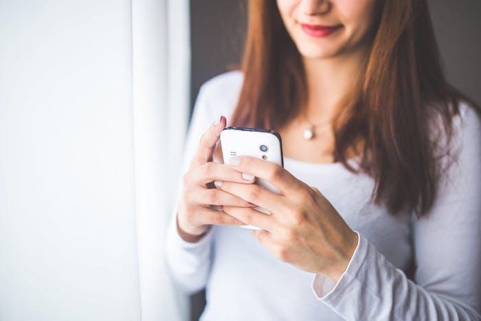 eine frau mit roten lippen und einer weißen halskette und pinkem nagellack, frau mit kleinem weißen smartphone