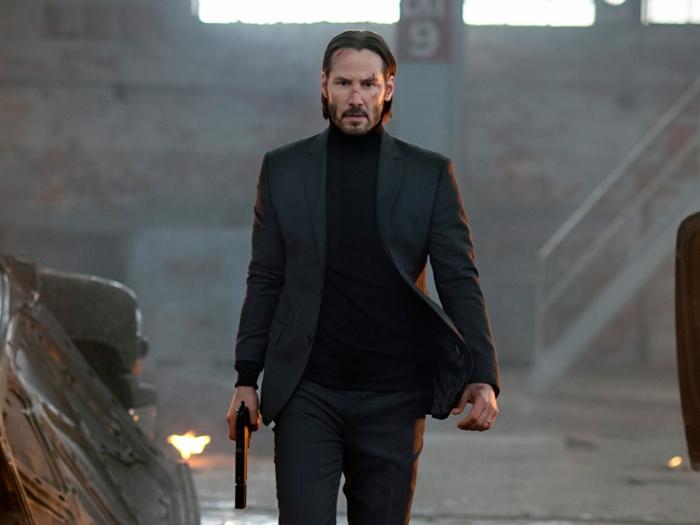 Keanu Reeves als John Wick, der Schauspieler in einem schwarzen Anzug mit Pistole in der Hand