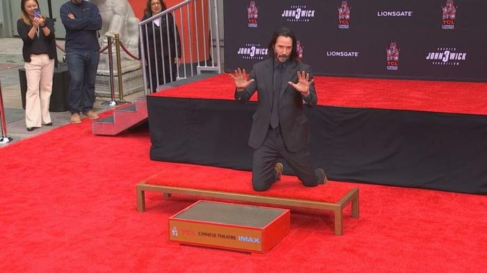 Keanu Reeves auf einem roten Teppich, fertig seine Handabdrücke gleich zu eingravieren