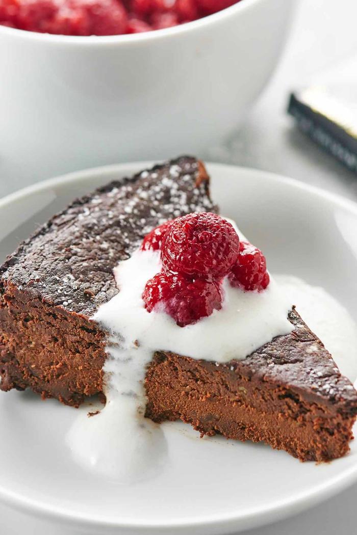 kuchen glutenfrei baken, schokokuchen mit kakao garniert mit weißer soße und himbeeren, torte ohne mehl
