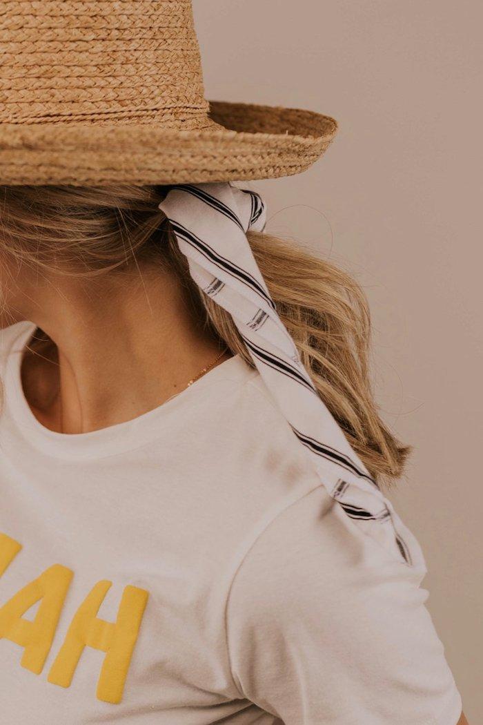 Sommerhut und gestreiftes Kopftuch, weißes Top mit gelber Aufschrift, lange blonde Haare