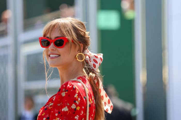 Weißes Haarband mit Küssen, Sonnenbrille mit roten Rahmen, rote Bluse mit Blumenmuster