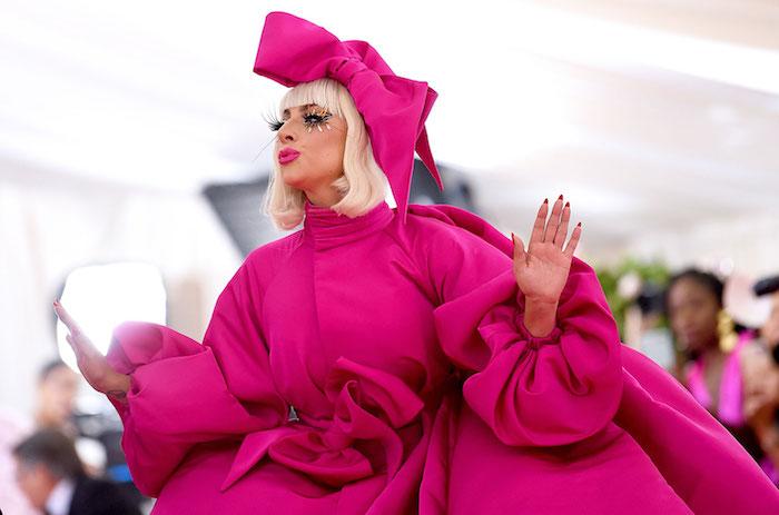 die pop-sängerin lady gaga mit blondem haar und violetten lippen und einem violetten kleid, met gala 2019