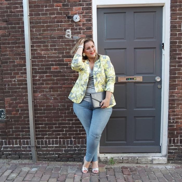 mode für mollige frauen, helle jeans, graue bluse, sakko it floralen motiven, kleie tasche