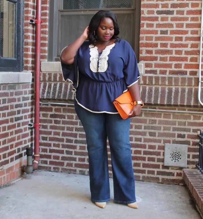 mode für mollige frauen, grangenfarbene tasche, dunkelblaue bluse mit weißen elementen, jeans