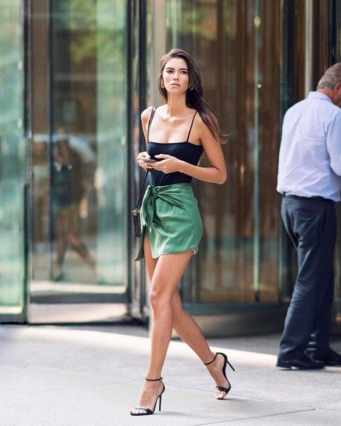 party outfits damen, kurzer grüner rock, schwarzer top, hohe schuhe, kleine tasche, abend outfit