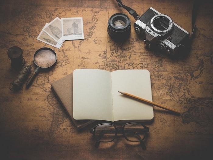 pinterest hintegründe, ein schreibtisch mit weltkarte darauf, ein heft mit kuli, kamera, fotos, brille