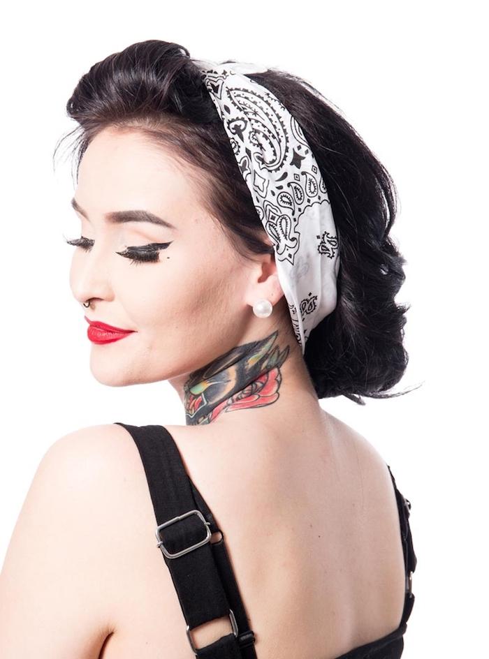 Rockabilly Frisur mit Kopftuch, farbiges Tattoo am Hals, roter Lippenstift und schwarzer Lidstrich