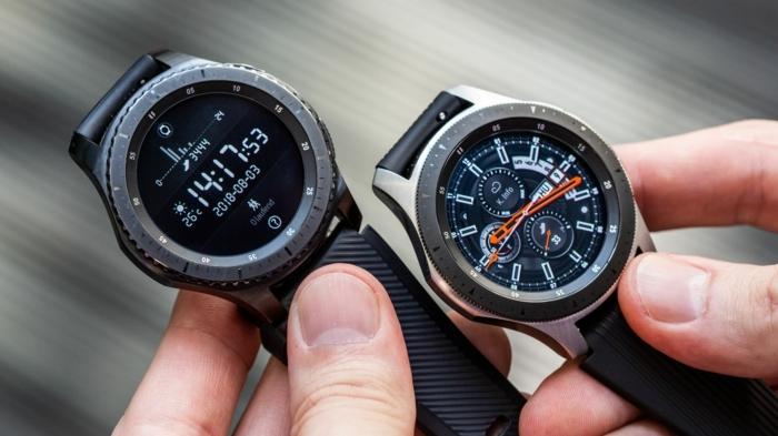 zwei schwarze Smartwatches, digitale Armbanduhr und klassische Armbanduhr, schwarze Bänder