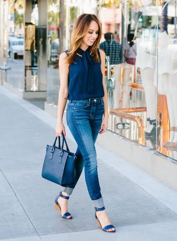 schickes outfit damen, blaue jeans, dunkelblaue bluse mit schleife, große tasche, bisiness outfit frauen