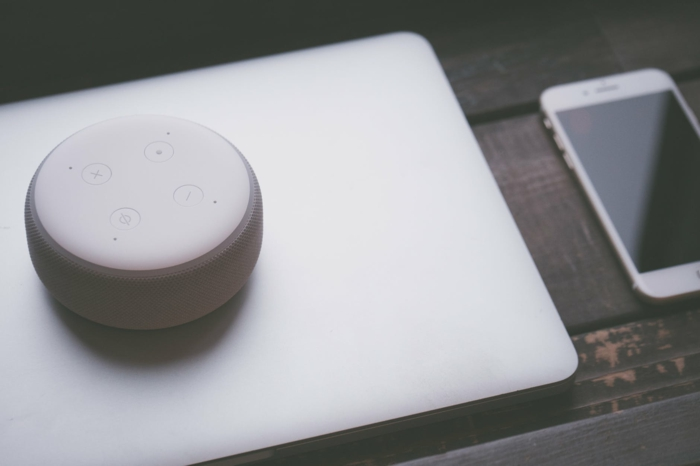 ein Handy und ein Computer auf einem schwarzen Tisch, die Steuerung für einem Smart Home