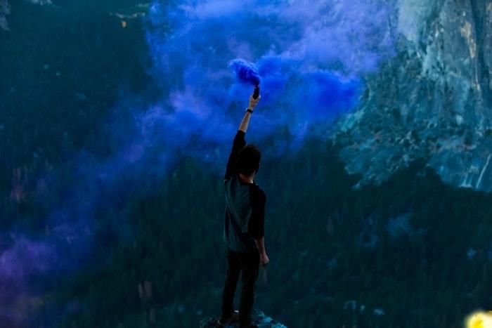 tumblr wallpaper mit einem mann, der oben auf einem rock steht und wolken auslöst