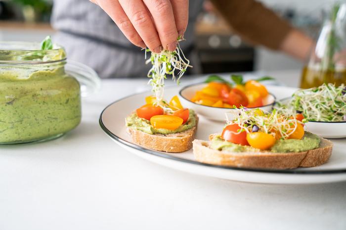 Hausgemachtes Avocado Pesto mit Basilikum auf Brotscheiben servieren