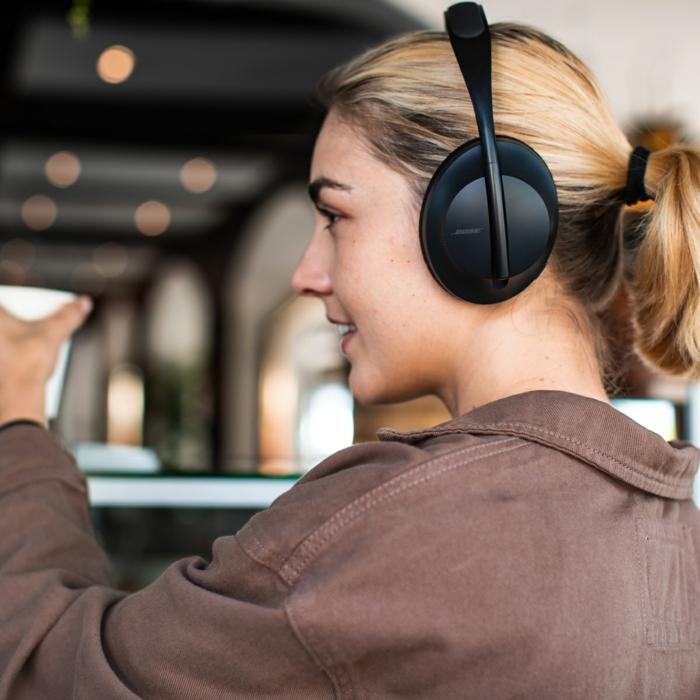 schwarzer Kopfhörer von Bose, ein Mädchen mit lila Jacke, ein blondes Mädchen mit Kopfhörer