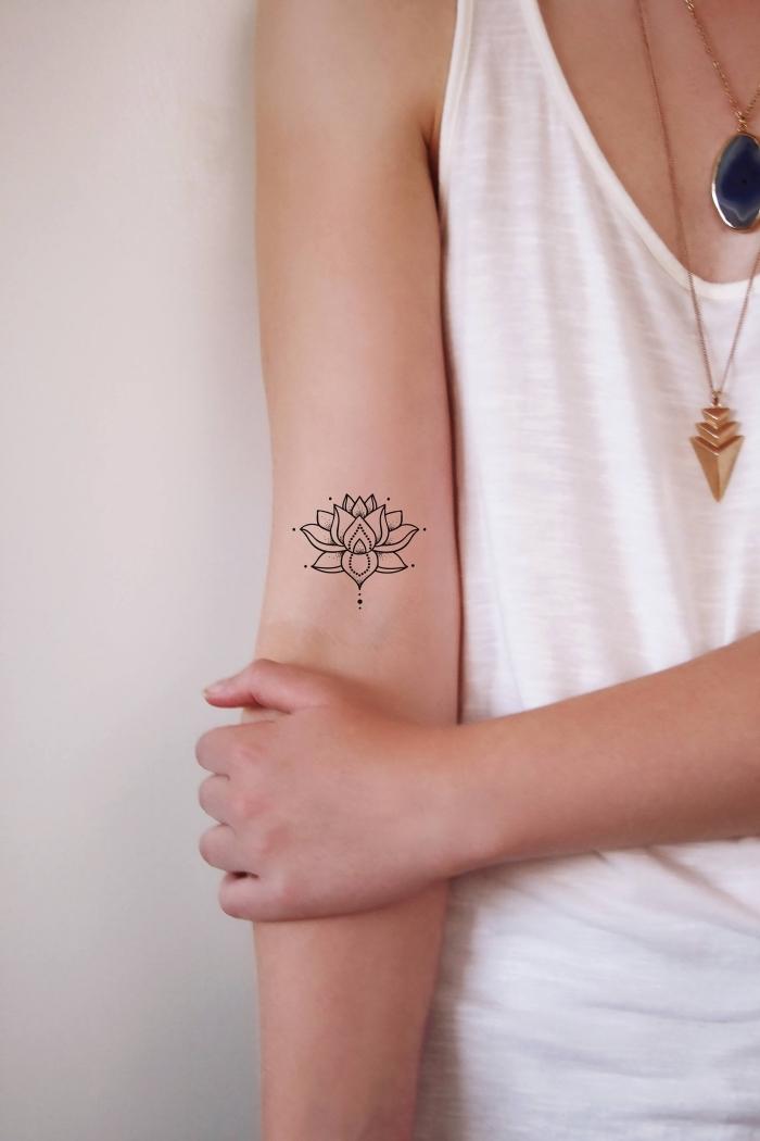 buddhismis symbole, klene tattoo motive für frauen, kleine lotusblumme am oberarm
