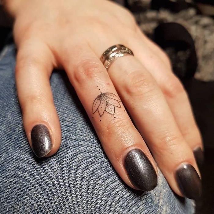 buddhistische symbole tattoo, kleine motive für frauen, lotusblüte am ringfinger, schwarzer nagellack