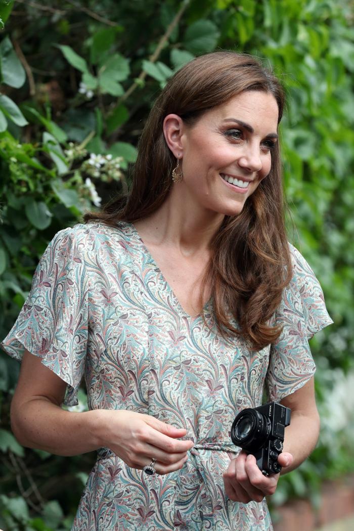 Catherine ist mit einem schönen bunten Kleid angezogen bei dem Workshop und trägt ihr Camera