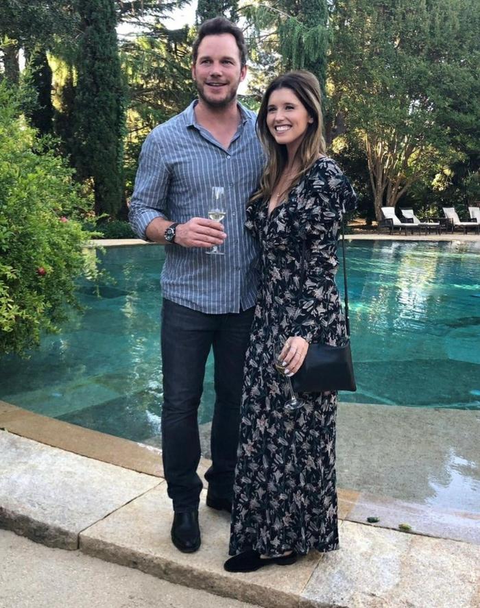 ein buntes Kleid von Kristhine und ein lässiger Outfit von Chris Pratt, neben einem Schwimmbecken