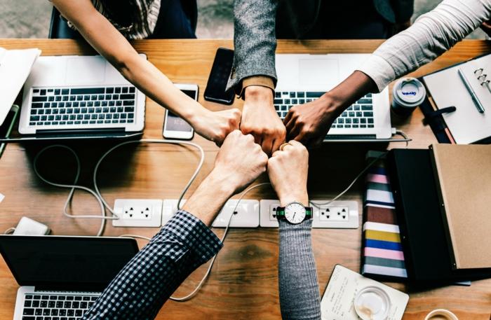 ein Team arbeitet zusammen auf einem Tisch aber ihre Task sind mit Dropbox verbunden